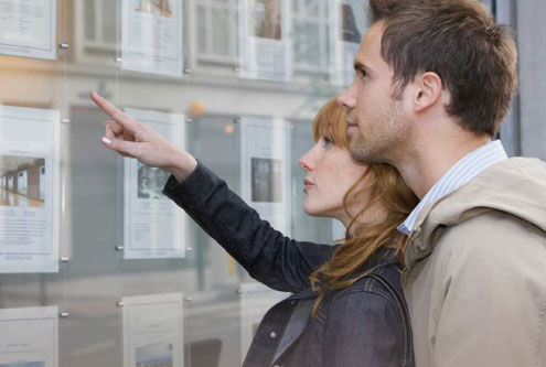 couple looking in estate agent window